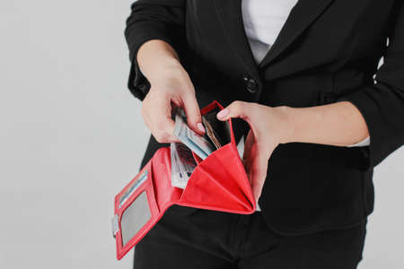Women hands take money from red purse on gray background isolated close up
