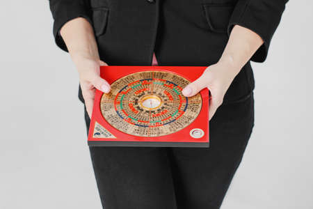 Chinese compass Lopan for Feng Shui technique in female hands isolated Imagens