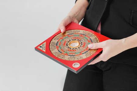 Chiński kompas Lopan do techniki Feng Shui w kobiecych rękach na białym tle