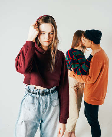 Sad young teen girl on background of loving couple, isolated. The concept of jealousy, loneliness