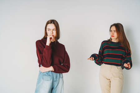 Two sisters twins beautiful girls hipsters in casual clothing on grey background isolated, quarrel, resentment Stock fotó