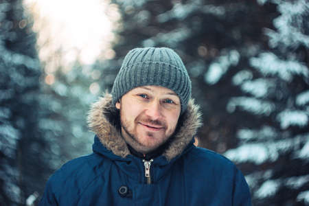 Portrait of smiling bearded man traveler forester hunter in the winter forest