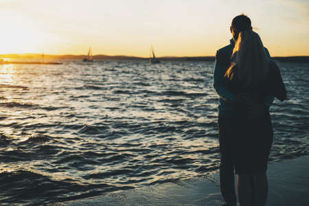 Silhouette of couple in love on the pier, sunset time, sailboats and water background