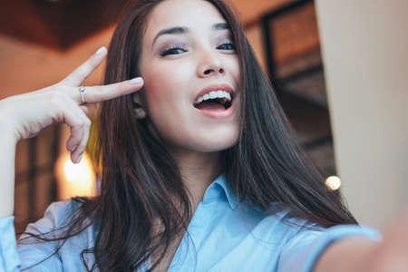 Beautiful charming brunette smiling asian girl taking selfie on frontal camera at cafe 版權商用圖片