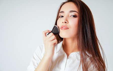 Maquillaje kabuki de pincel en mano de sonriente joven asiática con cabello largo oscuro sobre fondo blanco.