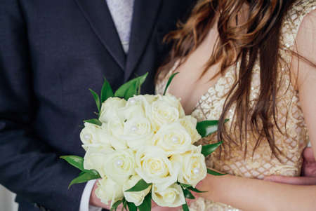 Bride and groom with bouquet of white roses in wedding day, close up