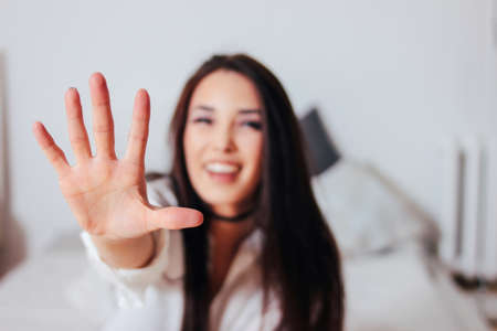Happy smiling beautiful long hair asian girl young woman pulling hand towards camera sitting on bed
