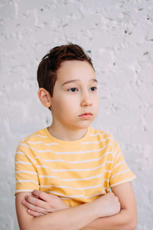 Cute tween indifferent sad boy in yellow t-shirt making kiss by hands isolated on the white wall background