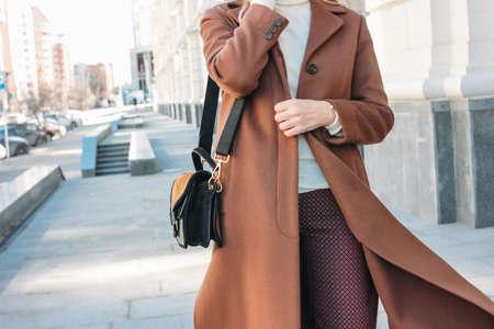 Stylish fashionable blonde woman wearing coat and sunglasses speaking on mobile phone, street style photo