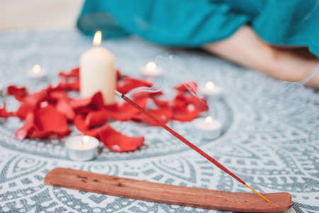 Burning incense red stick on candles background and woman practicing yoga 版權商用圖片