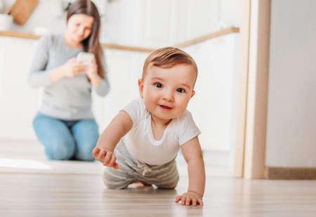 El lindo bebé está explorando el mundo, mientras la madre navega en su teléfono inteligente en la cocina.