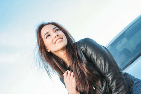 Happpy beautiful charming brunette long hair young asian woman in black leather jacket near her car