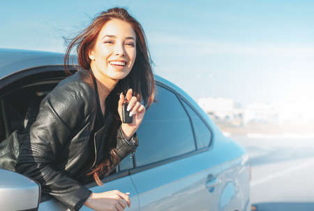 Happpy beautiful charming brunette long hair young asian woman in black leather jacket with key in car window 写真素材