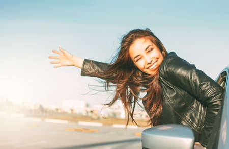 Happpy beautiful charming brunette long hair young asian woman in black leather jacket in car window at sunset