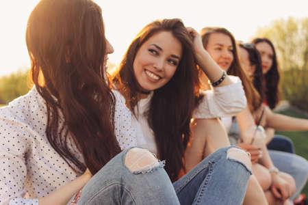Grupa przyjaciół młodych szczęśliwych dziewcząt cieszyć się życiem na letniej ulicy miasta, tło zachodu słońca