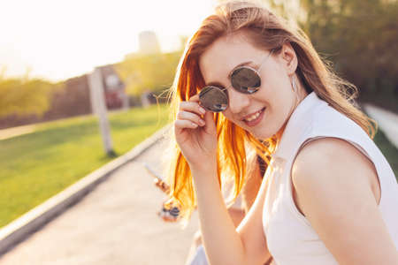 Positive beautiful happy red haired girl in mirror sunglasses with friends on city street background, summer sunset time