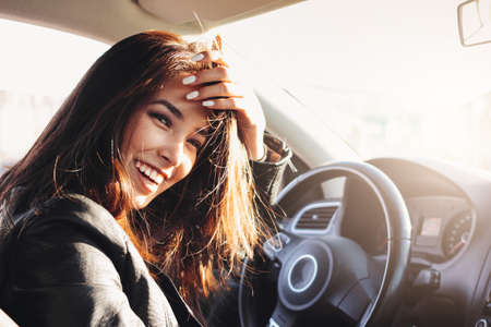Close up portrait of beautiful brunette long hair happy young asian woman driving the passenger car Imagens