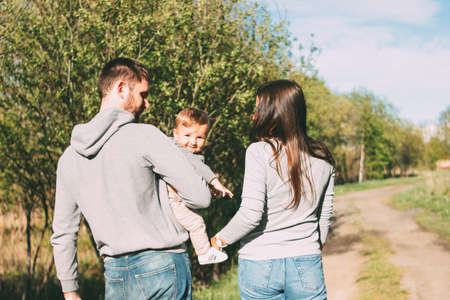 Happy family with cute baby boy walking on road outdoors, sensitivity to the nature concept