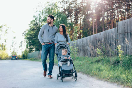 Authentic family with cute baby boy 8-9 months sitting in stroller walking on the village road outdoors, sensitivity to the nature concept