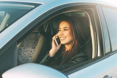 The beautiful brunette long hair young asian woman driving and speaking by mobile phone