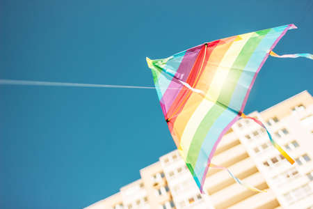 Rainbow colored kite flying in blue sky in city. Freedom and summer holiday Imagens - 124888888