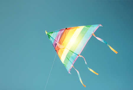Rainbow colored kite flying in the clean blue sky. Freedom and summer holiday