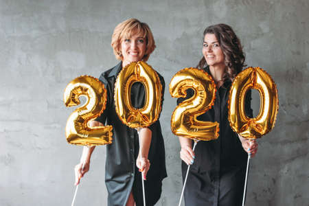 Two young women in black dresses holding the 2020 numbers balloons on the grey concrete wall background. New Year party with friends, corporate