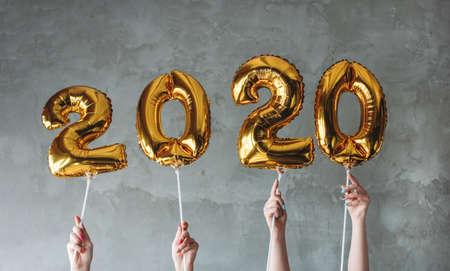 Las manos de la mujer sosteniendo globos de números 2020 en el fondo de muro de hormigón gris. Fiesta de año nuevo con amigos, corporativa.