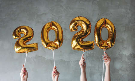 The woman hands holding 2020 numbers balloons on the grey concrete wall background. New Year party with friends, corporate