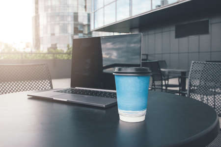 Paper cup of coffee and open laptop on the table of street cafe in business district of city Фото со стока