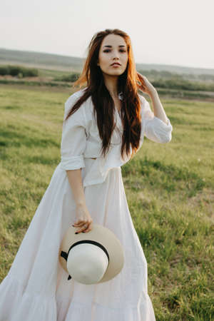Beautiful carefree long hair asian girl in white clothes and straw hat enjoys life in the nature field at sunset. Sensitivity to nature concept