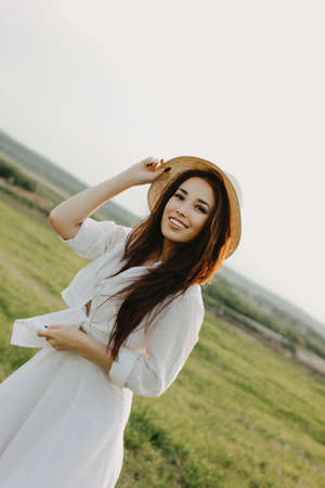 Portrait of charming carefree long hair asian girl in white clothes and straw hat enjoys life in the field at sunset. Sensitivity to nature concept Stock Photo