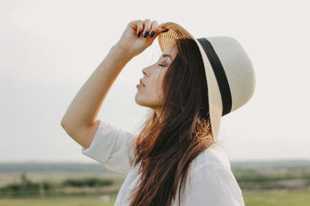Portrait of charming carefree long hair asian girl in white clothes and straw hat enjoys life in field. Sensitivity to nature concept