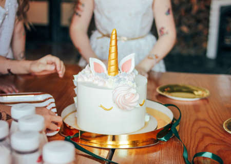 Childrens hands little girls reach for the cake. Big beautiful cake unicorn on birthday of little Princess on festive table