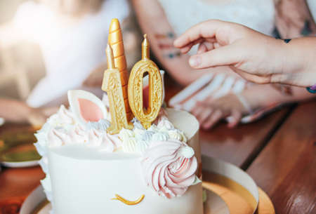 Childrens hands little girls reach for the cake. Big beautiful cake unicorn on the years birthday of little Princess on festive table Stockfoto