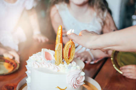 Childrens hands little girls reach for the cake. Big beautiful cake unicorn on ten years birthday of little Princess on festive table