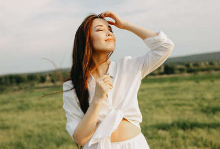 Portrait of beautiful carefree long hair girl in white clothes on the field at sunset. Sensitivity to nature concept
