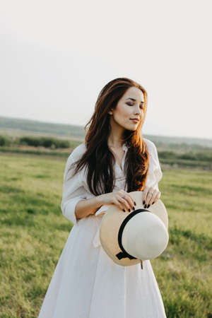 Beautiful carefree long hair asian girl in white clothes and straw hat enjoys life in the field at sunset. Sensitivity to nature concept