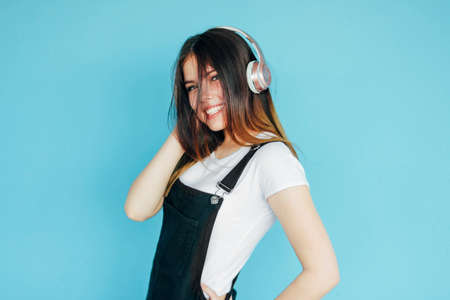 Happy carefree smiling teenager girl with dark long hair in white t-shirt listening music in headphones isolated on the blue background
