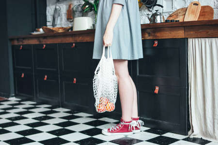 Young woman in grey dress with knitted rag bag string bag shopper in the kitchen, zero waste, slow life