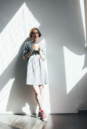 Young woman in simple grey dress with yellow cup standing against the wall, full-length portrait, hard light