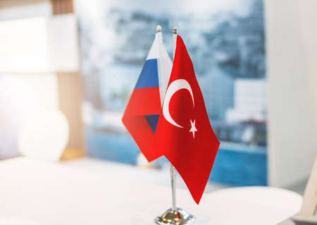 Russian and Turkish flags on metal stand on the business conference or exhibition, international relations, trade, cooperation concept Foto de archivo