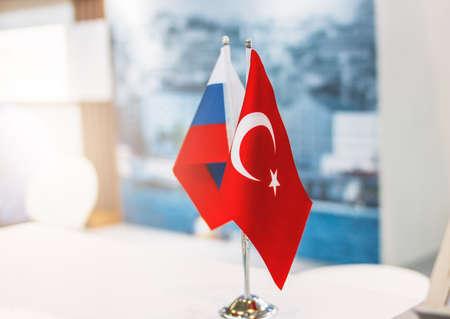 Russische und türkische Flaggen auf Metallständer auf der Geschäftskonferenz oder Ausstellung, internationale Beziehungen, Handel, Kooperationskonzept