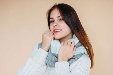 Beautiful smiling girl with clean skin and dark long hair in cozy white sweater and warm scarf on the beige background