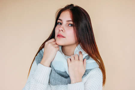 Beautiful smiling girl with clean skin and dark long hair in cozy white sweater and warm scarf on beige background Zdjęcie Seryjne