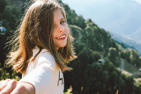 Smiling tween girl reaches out to camera follow me on the background of beautiful mountains, family travel concept