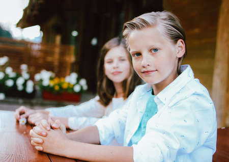Attractive preteen blonde boy with blue eyes in white shirt with sister friend sitting at the table in backyard of wooden cottage