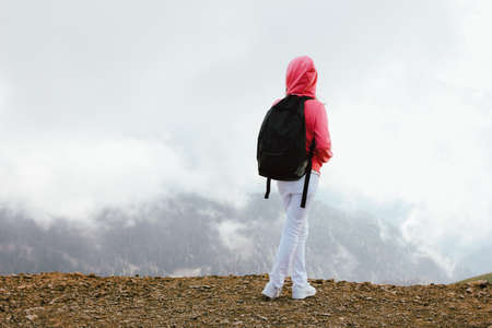 Tween girl with backpack looking on beautiful mountains in the clouds, family travel concept