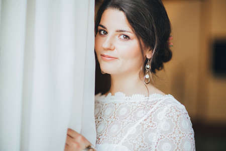Beautiful smiling bride brunette young woman in white lace dress near window, close up