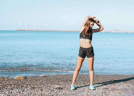 Young slim athletic woman in sportswear doing exercises on the sea beach in the morning, healthy lifestyle Stock Photo